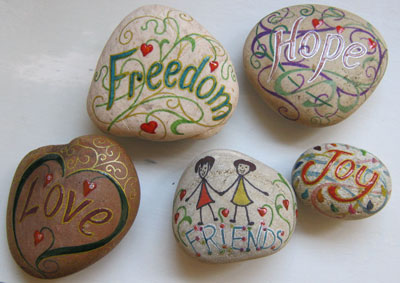 Examples of painted inspirational words on pebbles
